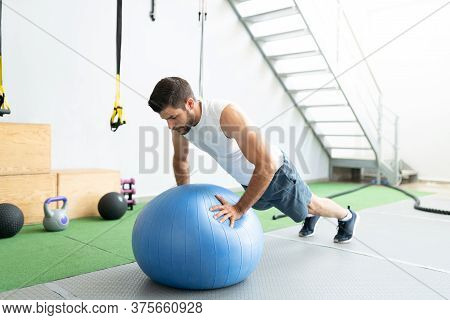 Latin Young Man Doing Push-ups On Fitness Ball During Cross-training At Gym
