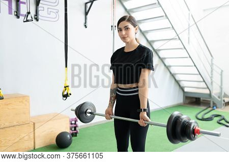 Confident Latin Young Woman Lifting Barbell During Cross-training