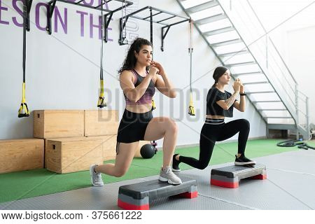 Hispanic Active Young Women Doing Lunges On Step Platforms At Cross-training Gym