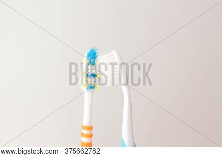 Red And Blue Toothbrushes On A Gray Background. Old And New Toothbrush. Oral Hygiene Concept. Copy S