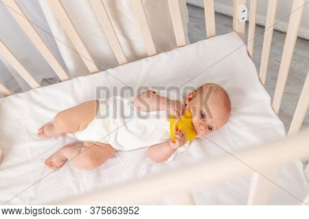 Baby 6 Months Old Girl Lying In The Crib, Morning Baby, Baby Put To Bed, Little Baby Looks Through T