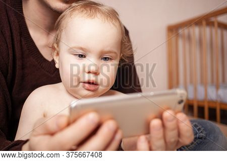 Parents With Daughter Watching Video On Mobile Phone At Home