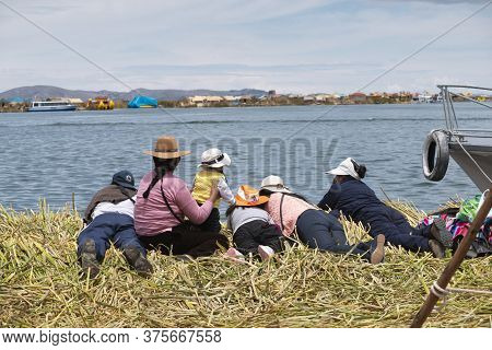 Puno, Peru - November 5: Local People Relax In Front Of Water On Floating Uros Islands At Lake Titic