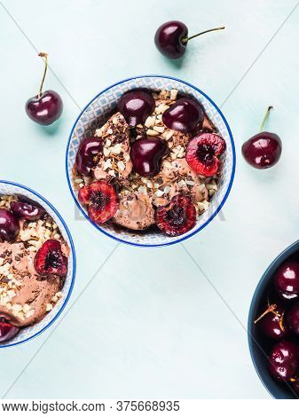 Chocolate Ice Cream Sundae With Cherries, Almond And Chocolate Sprinkles On Green Turquoise Backgrou