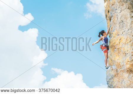 Athletic Woman In Colorful Sportswear Climbs A Rock With Rope On Cloud Sky Background. Sport Climbin