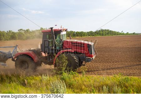 Tractor Plows The Land For Sowing, With A Plow On A Sunny Day, Agriculture