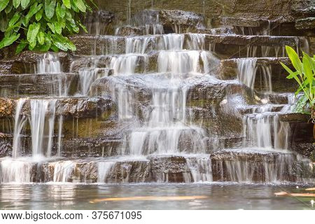 Artificial Water Fall In The Garden. Artificial Pond With A Waterfall In A Landscape Design. A Small