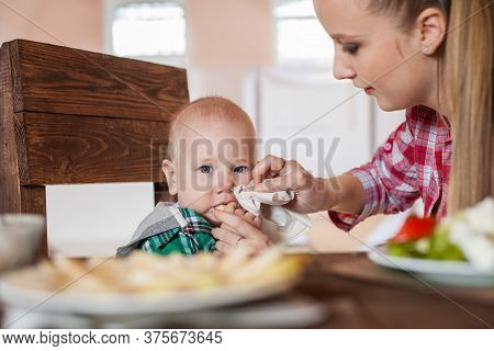 Mother Feeding Child. First Solid Food For Young Kid.