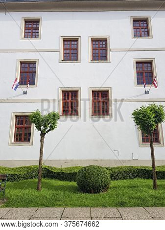 A Low Angle Shot Of A Building White Facade With Hanging Flags