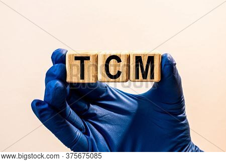 The Word Tcm Which Is Made From Wooden Cubes. Hands In A Blue Glove. Isolated On White Background.