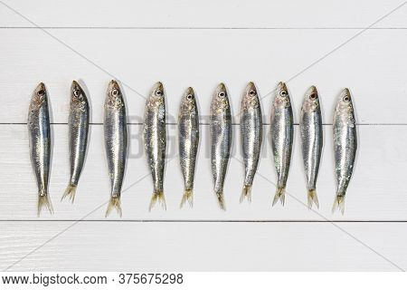 Some Sardines Arranged On A White Wooden Table
