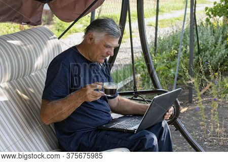 A Man Sits In A Garden Swing And Communicates Remotely With Friends, Through A Laptop In A Country H