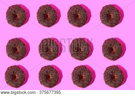 Donut. Cake Donut with Chocolate Frosting and Chocolate Sprinkles. Donut Art. Repeating Doughnut pattern. Backgrounds and Wallpapers.  Pink background.