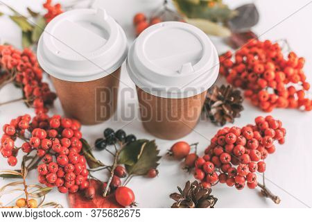 Two Paper Glasses For Hot Drinks Among Autumn Leaves, Berries And Cones, Autumn Concept
