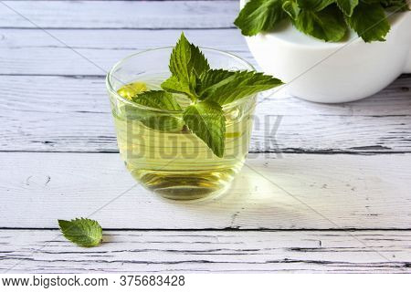 Fresh Mint Tea Concept On A Wooden Background. Mint Tea In A Transparent Cup And One Mint Leaf On Th