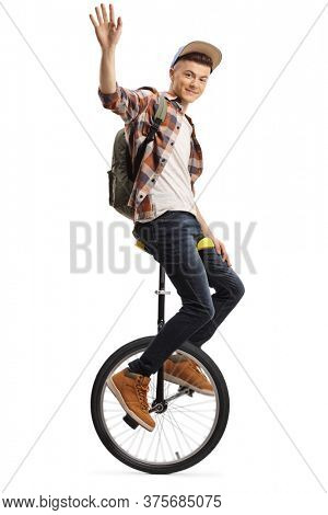 Young male student balancing a unicycle and waving isolated on white background