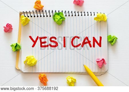 Words Of Yes You Can On Sticky Color Papers Hanging By A Rope Against Blurred Green Background.