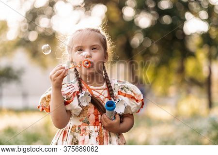 A Girl With Down Syndrome Blows Bubbles. The Daily Life Of A Child With Disabilities. Chromosomal Ge