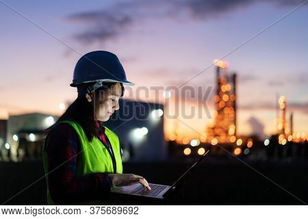Asian Woman Petrochemical Engineer Working At Night With Laptop Inside Oil And Gas Refinery Plant In
