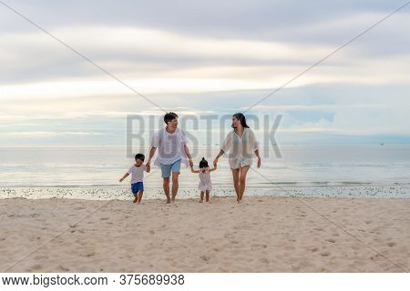 Happy Asian Family Holidays During Joyful Father, Mother, Son And Daughter Walking Together Along Su