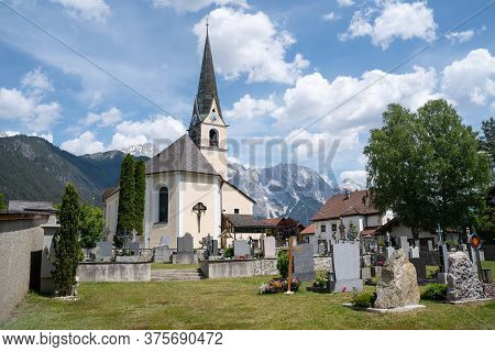 Obsteig, Tirol, Austria - 3 June 2020: Traditional Austrian Village Church And Cemetery In The Sunny