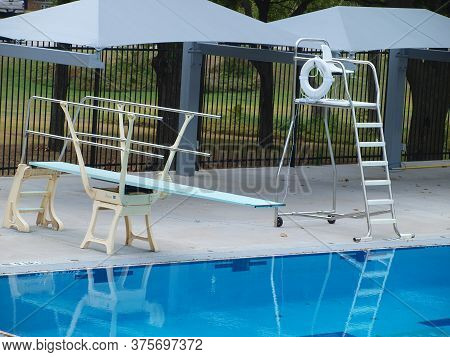 A Diving Board Sits Next To A Lifeguards Chair At The Deep End Of This Pool.