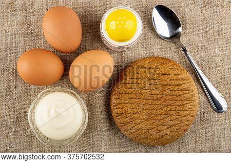 Brown Unpeeled Boiled Eggs, Salt Shaker, Teaspoon, Bowl With Mayonnaise, Rye Flapjack On Burlap. Top