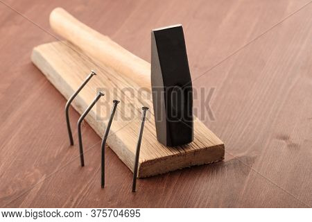 Nails Bent Around A Hammer Lying On The Board. The Concept Of A Tyrant\'s Funeral Which Is Honored B