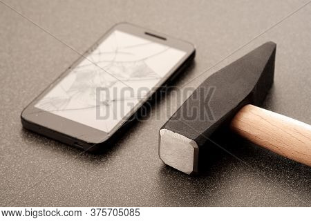 Hammer Broken Mobile Phone On A Dark Ceramic Surface. Broke The Phone So You Wouldn Be Disturbed