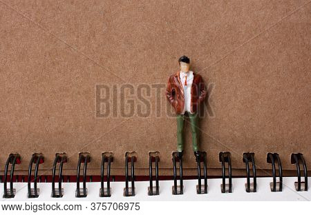 Figurine Standing Beside Spiral Notebook In View