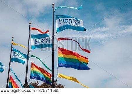 Rainbow Gay Pride Flag And Pier 39 Flag Fluttering On Blue Sky Background