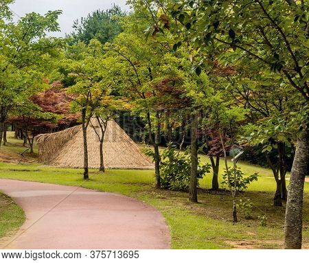 Straw Thatched Hut Next To Hiking Path In Prehistoric Archeological Site In Daejeon, Korea.