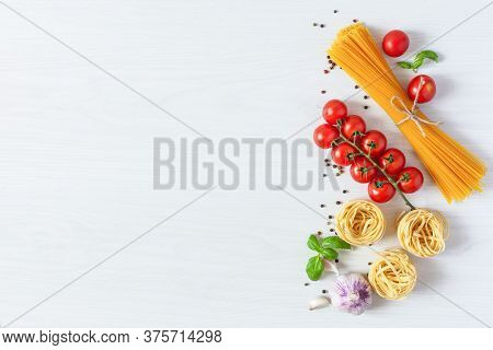 Italian Pasta Ingredients For Cooking. Raw Pasta, Vegetables, Spices And Herbs Top View On White Woo