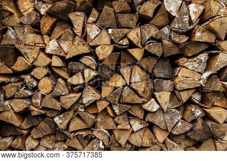 Firewood Stacked At Woodpile. Wood Background And Texture.