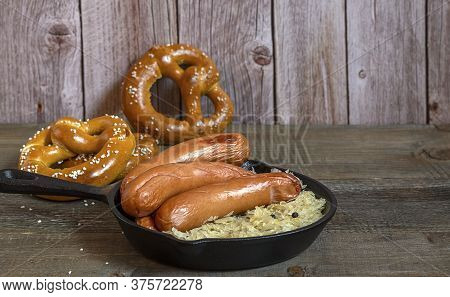 Traditional German Sausages Bratwurst With Sauerkraut, And Pretzels On The Wooden Table.