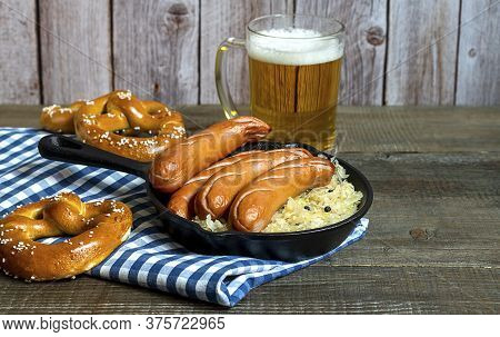 Traditional German Sausages Bratwurst With Sauerkraut, Beer, And Pretzels On The Wooden Table. Oktob