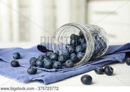 Overturned Glass Jar Of Ripe Blueberries On White Wooden Table