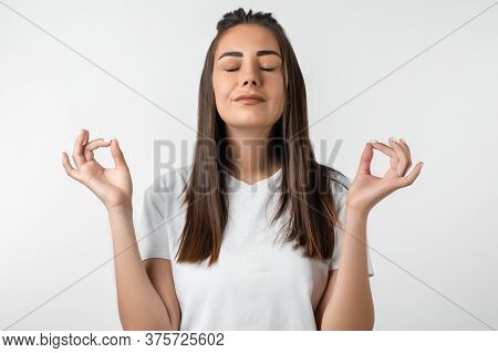 Attractive Calm European Girl With Long Chestnut Hair Delighted Meditating Hands Sideways Nirvana Lo