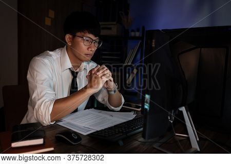Attractive Young Asian Businessman Concentrated Working Until Late Overtime On Publication At His De