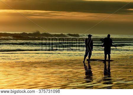 Dunedin, New Zealand - Jan 2020. An Unidentified Photographer Taking Photographs Of A Sunset At The