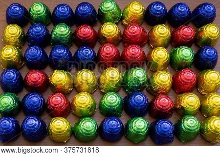 Chocolate Bonbons In Multicolored Foil Wrap Arranged In Rows On Wooden Table. Colorful Sweets Close-