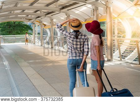 The Back Of Two Teenage Girls Who Are Friends, Walking In The Street Or The Walkway, Holding Carryin