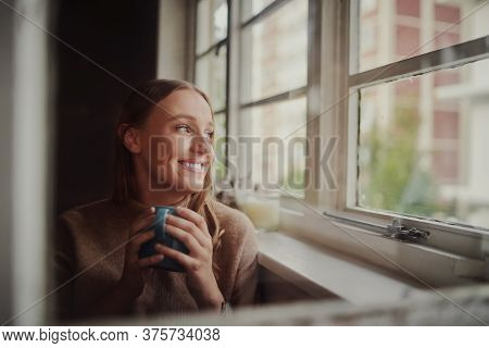 Quarantined Young Woman Smiling Drinking Coffee And Daydreaming Looking Out At Empty Streets