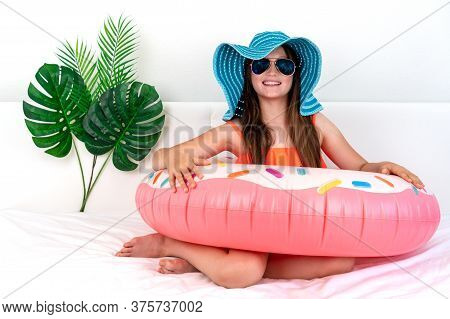 Happy Little Girl Sits On A Bed In A Hat. Imitation Of Holidays During A Pandemic. Domestic Tourism