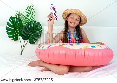 Happy Little Girl Sits On A Bed In A Hat And Holds A Water Gun In Her Hands. Holidays During A Pande