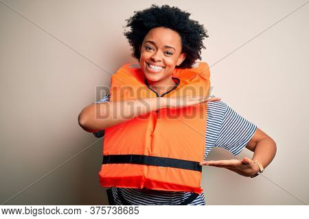 Young African American afro woman with curly hair wearing orange protection lifejacket gesturing with hands showing big and large size sign, measure symbol. Smiling looking at the camera. Measuring