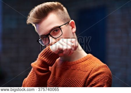 Portrait of a smart young guy in a pullover and glasses. Studio shot. Men's beauty. Study, education.