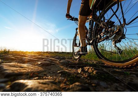back view of a man with a bicycle against the blue sky. cyclist rides a bicycle.