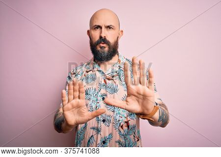 Handsome bald man with beard and tattoo wearing casual floral shirt over pink background Moving away hands palms showing refusal and denial with afraid and disgusting expression. Stop and forbidden.