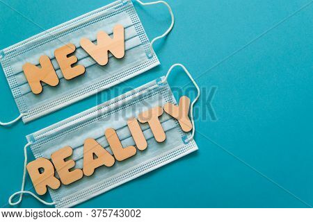 New Reality Words On Protective Face Masks On Blue Background. Post Covid-19 Pandemic Changes, New N